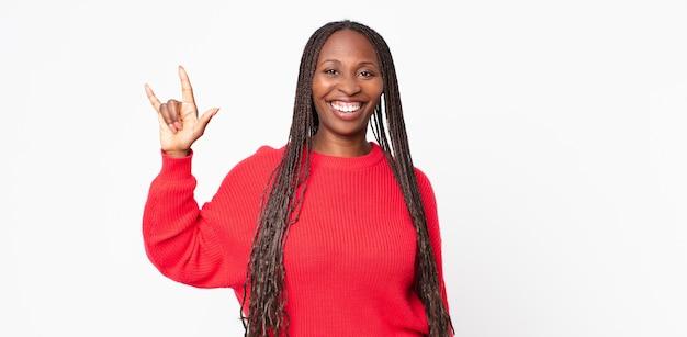Mulher negra adulta afro se sentindo feliz, divertida, confiante, positiva e rebelde, fazendo sinal de rock ou heavy metal com a mão