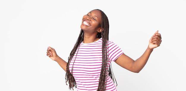Mulher negra adulta afro sorrindo, sentindo-se despreocupada, relaxada e feliz, dançando e ouvindo música, se divertindo em uma festa