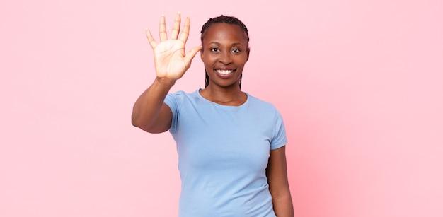 Mulher negra adulta negra sorrindo e parecendo amigável, mostrando o número cinco ou quinto com a mão para a frente, em contagem regressiva
