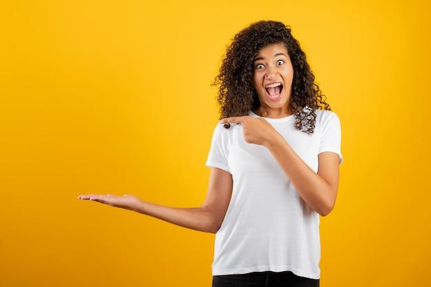 Mulher negra africana animada, apontando o dedo na copyspace à mão isolado sobre o amarelo
