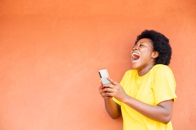 Mulher negra africana animada após receber boas notícias de seu celular