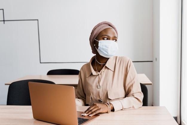 Mulher negra africana com laptop. uso do computador para trabalho on-line. máscara médica para proteção contra coronovírus covid-19.