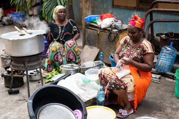 Mulher negra africana cozinhando e vendendo comida de rua