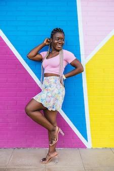 Mulher negra africana muito feliz posando em uma parede em várias cores. foto de estilo de vida de uma mulher africana feliz