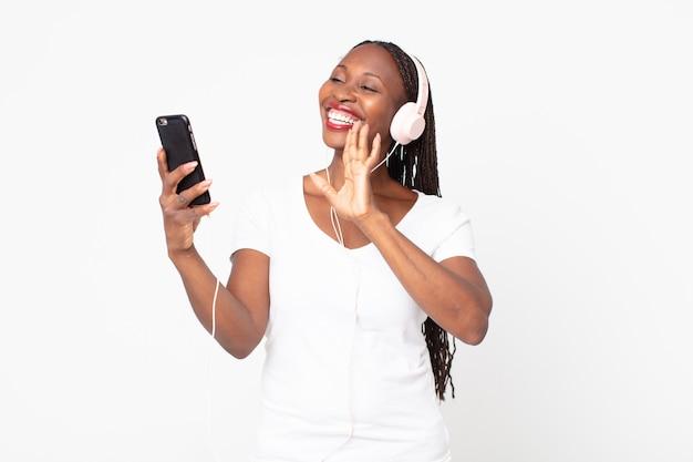 Mulher negra afro-americana a ouvir música com auscultadores e smartphone Foto Premium