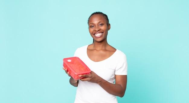 Mulher negra afro-americana a segurar uma tupperware