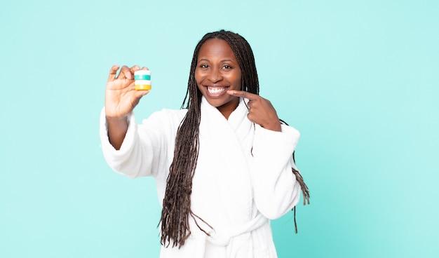 Mulher negra afro-americana adulta vestindo roupão de banho e segurando produtos cosméticos