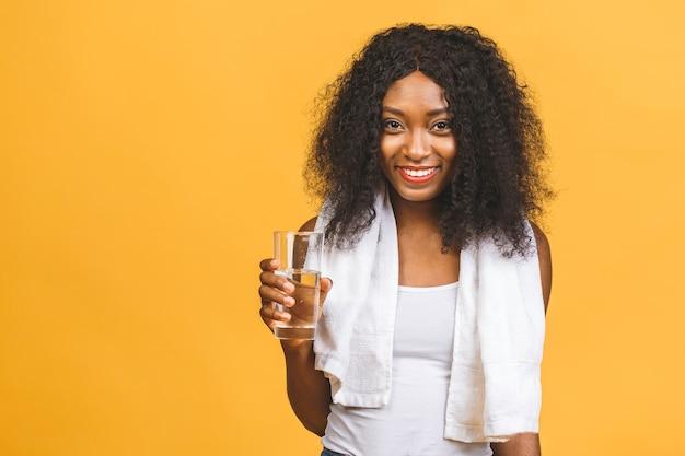 Mulher negra afro-americana bonita e atraente com suor a beber água após exercício físico