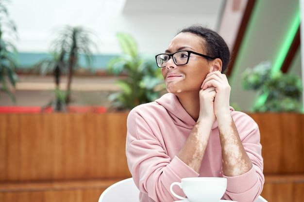 Mulher negra afro-americana com problema de pele com pigmentação vitiligo interna vestida de óculos rosa com capuz sentado na mesa bebida interna
