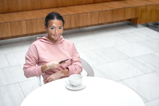 Mulher negra afro-americana com problema de pele vitiligo pigmentação interna vestida com capuz rosa na mesa usando smartphone