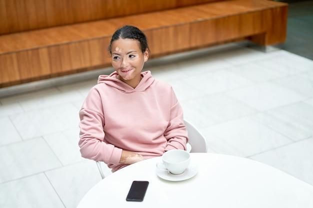 Mulher negra afro-americana com problema de pele vitiligo pigmentação interna vestida com capuz rosa sentado na mesa vista de alto ângulo
