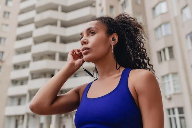Mulher negra afro-americana com roupa urbana de fitness esportivo no telhado, fazendo exercício, ouvindo música em fones de ouvido
