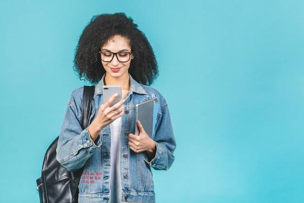 Mulher negra afro-americana do estudante que usa o smartphone que está sobre isolado sobre o fundo azul.