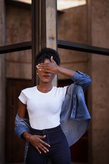 Mulher negra afro-americana fecha os olhos com a mão