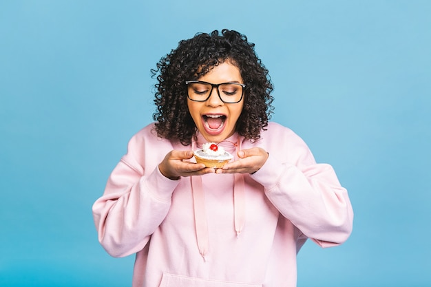Mulher negra afro-americana feliz com estilo de cabelo afro encaracolado, fazendo uma bagunça comendo uma enorme sobremesa chique sobre fundo azul. comendo bolinho.