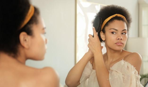Mulher negra afro-americana penteando o cabelo com uma escova e fazendo penteado