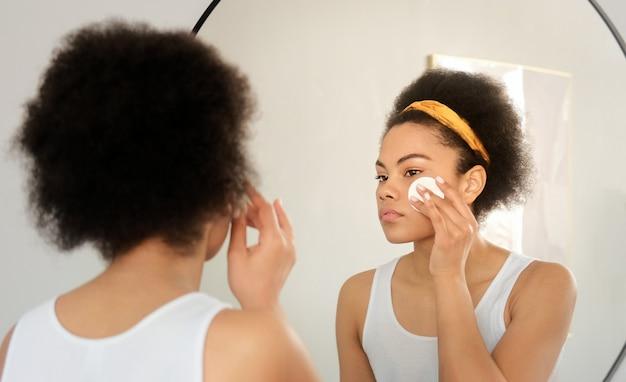 Mulher negra afro-americana segurando um disco de algodão limpando a pele do rosto com limpador