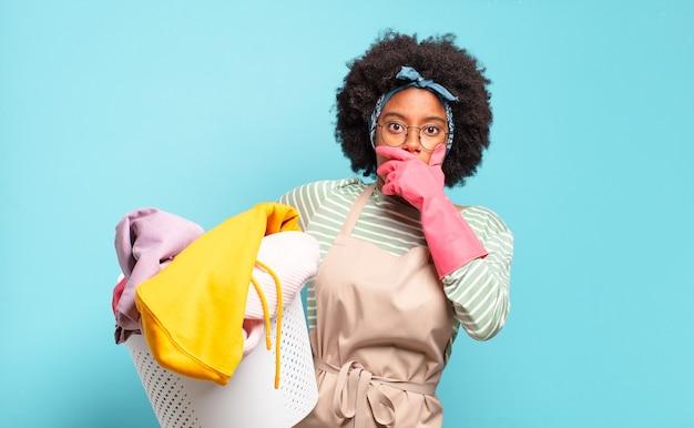 Mulher negra afro cobrindo a boca com as mãos com uma expressão chocada e surpresa, mantendo um segredo ou dizendo oops. conceito de limpeza. conceito doméstico