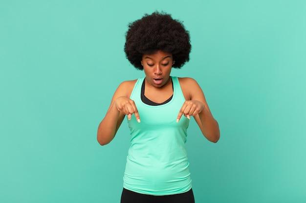 Mulher negra afro com a boca aberta apontando para baixo com as duas mãos, parecendo chocada, espantada e surpresa