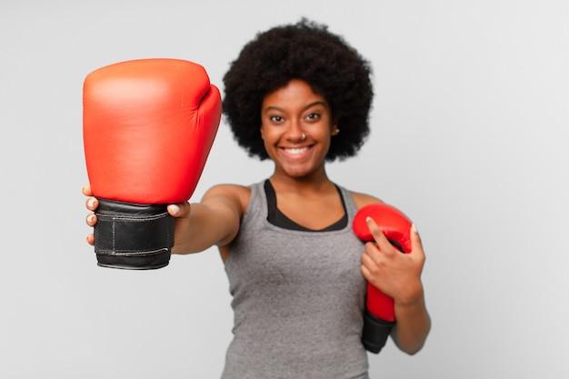 Mulher negra afro com luvas de boxe.
