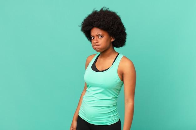 Mulher negra afro com uma expressão boba de louca surpresa, estufando as bochechas, sentindo-se recheada de gordura e cheia de comida