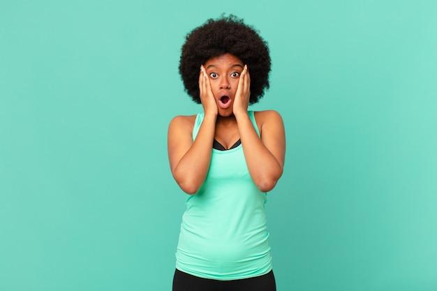 Mulher negra afro contra parede isolada
