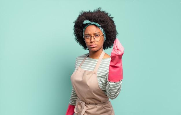 Mulher negra afro fazendo capice ou gesto de dinheiro, mandando você pagar suas dívidas !. conceito de limpeza. conceito doméstico