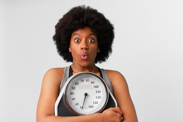 Mulher negra afro-fitness com balança ou balança