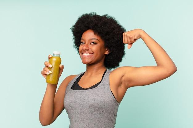Mulher negra afro-fitness com smoothy