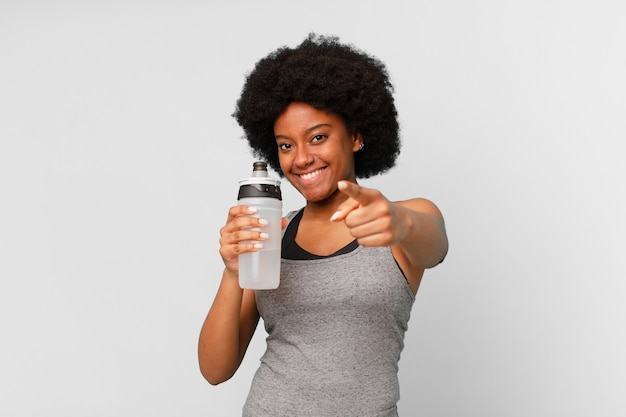 Mulher negra afro-fitness com toalha e lata de água