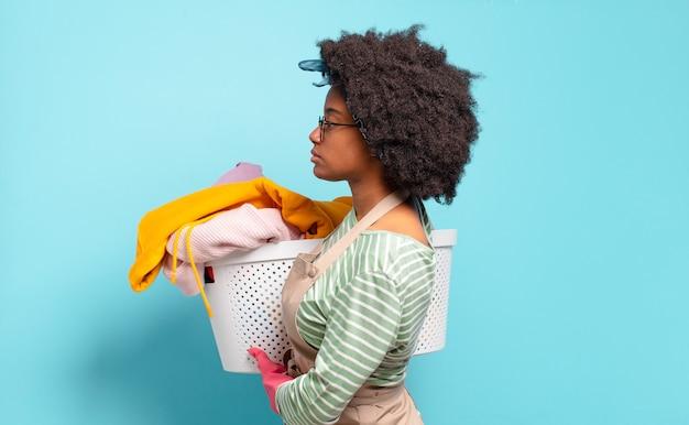 Mulher negra afro na vista de perfil, olhando para copiar o espaço à frente, pensando, imaginando ou sonhando acordado. conceito de limpeza. conceito doméstico
