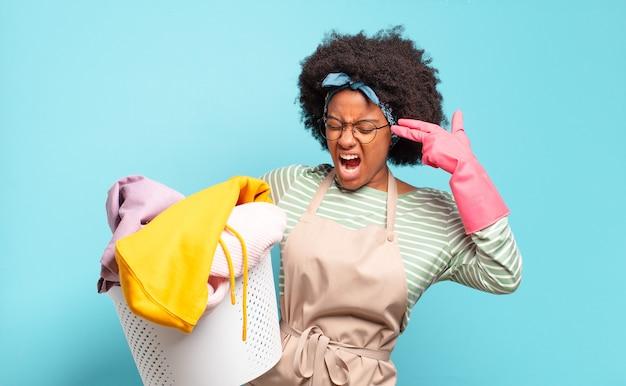 Mulher negra afro olhando infeliz e estressada, gesto de suicídio fazendo sinal de arma com a mão, apontando para a cabeça. conceito de limpeza. conceito doméstico
