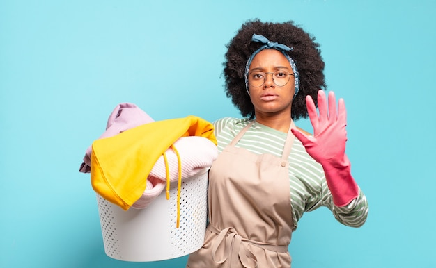 Mulher negra afro olhando séria, severa, descontente e com raiva, mostrando a palma da mão aberta, fazendo gesto de parada. conceito de limpeza. conceito doméstico