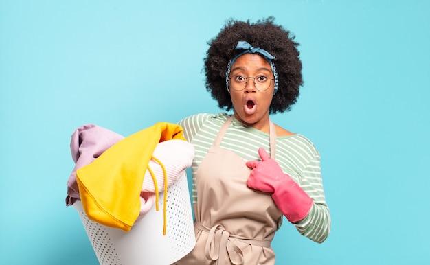 Mulher negra afro parecendo chocada e surpresa com a boca bem aberta, apontando para si mesma