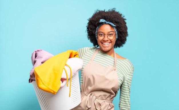 Mulher negra afro parecendo feliz e agradavelmente surpresa, animada com uma expressão de fascínio e choque. conceito de limpeza. conceito doméstico