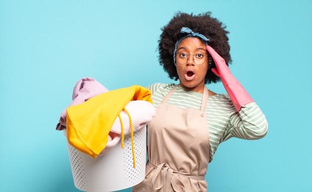 Mulher negra afro parecendo feliz, espantada e surpresa, sorrindo e percebendo uma boa notícia incrível. conceito de limpeza. conceito doméstico