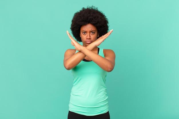 Mulher negra afro parecendo irritada e cansada de sua atitude, dizendo chega! mãos cruzadas na frente, dizendo para você parar