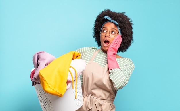 Mulher negra afro se sentindo feliz, animada e surpresa, olhando para o lado com as duas mãos no rosto. conceito de limpeza. conceito doméstico
