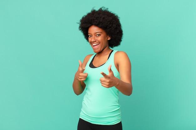 Mulher negra afro se sentindo feliz legal satisfeita relaxada e bem-sucedida apontando para frente escolhendo você