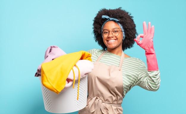 Mulher negra afro se sentindo feliz, relaxada e satisfeita, mostrando aprovação com um gesto ok, sorrindo. conceito de limpeza. conceito doméstico