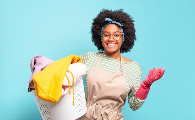 Mulher negra afro se sentindo feliz, surpresa e alegre, sorrindo com atitude positiva, percebendo uma solução ou ideia. conceito de limpeza. conceito doméstico