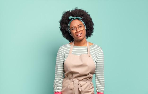 Mulher negra afro se sentindo perplexa e confusa, com uma expressão muda e atordoada olhando para algo inesperado. conceito de limpeza. conceito doméstico