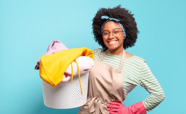Mulher negra afro sorrindo alegremente com uma mão no quadril e atitude confiante, positiva, orgulhosa e amigável. conceito de limpeza. conceito doméstico