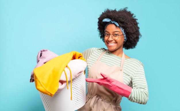 Mulher negra afro sorrindo alegremente, sentindo-se feliz e mostrando um conceito no espaço da cópia com a palma da mão. conceito de limpeza. conceito doméstico