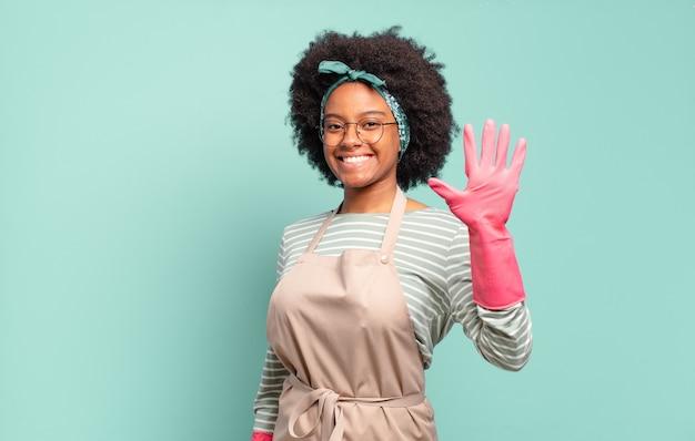 Mulher negra afro sorrindo e parecendo amigável, mostrando o número cinco ou quinto com a mão para a frente, em contagem regressiva. conceito de limpeza. conceito doméstico