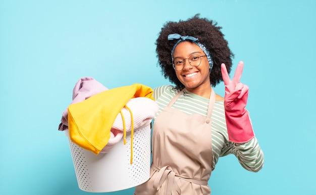 Mulher negra afro sorrindo e parecendo amigável, mostrando o número dois ou o segundo com a mão para a frente, em contagem regressiva. conceito de limpeza. conceito doméstico