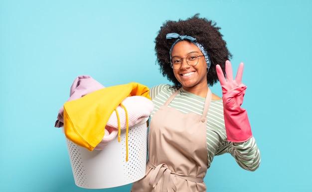 Mulher negra afro sorrindo e parecendo amigável, mostrando o número três ou terceiro com a mão para a frente, em contagem regressiva. conceito de limpeza. conceito doméstico