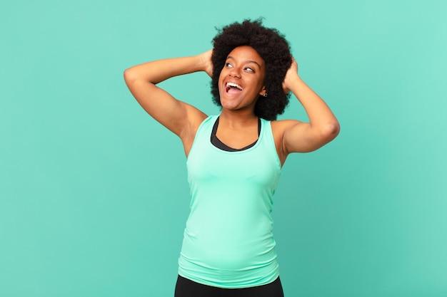 Mulher negra afro sorrindo e se sentindo relaxada, satisfeita e despreocupada, rindo positivamente e relaxando
