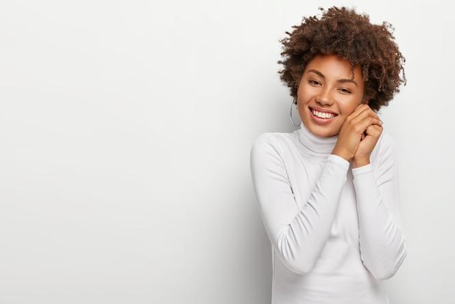 Mulher negra alegre com sorriso agradável, mantém as mãos juntas perto do rosto, parece feliz