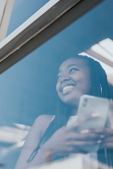 Mulher negra alegre enviando mensagens de texto em seu telefone